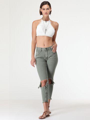 ג'ינס סקיני עם קרעים בברכיים וסיומת רוכסנים